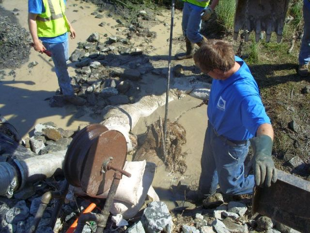 More roots and mud  removed from the pipe.  The vac truck (the pipe to the left) is removing the water with the highest concentration of sediment.